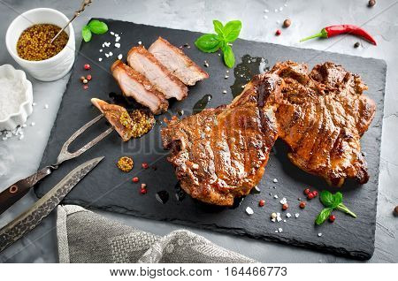 Grilled Steak on bone with knife and fork carving set on black stone slate. Sliced grilled Steak on bone pork rib