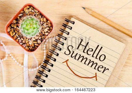 Hello summer on brown notebook with cactus and pencul on wooden background.