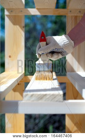 Female hand in textile glove paint inner part of wooden shelving outdoors closeup