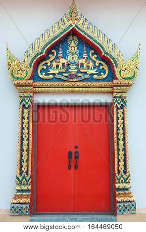 The golden carve door with red leaf in the thai temple