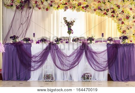 Rich Bunch Of Peonies And Tea Roses In Vase On Bride Groom Table