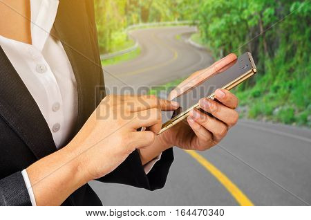 Business woman using mobile smart phone on s curve road Transportation business concept.