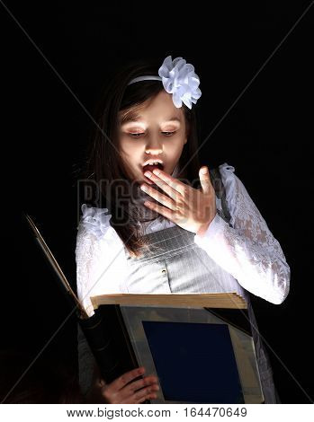 little girl sees an interesting book.photo on a black background