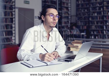 young entrepreneur or university student working on laptop with book on the scientific thesis in a library