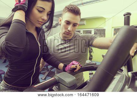 Personal trainer giving a workout instructions to a female gym client. Focus on the trainer