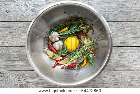 Cooking background. Lemon, herbs, chili, garlic and other seasoning in metal bowl on rustic wood, top view. Vegetables and herbs ready for making steak marinade
