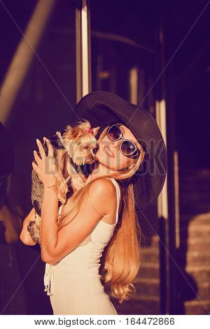 Beautiful young sexy blonde natural beauty dressed in fashionable stylish dress with small dog