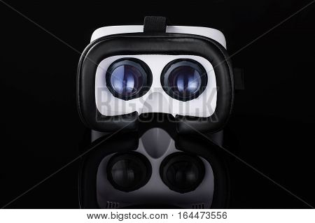 Virtual reality VR glasses or goggles isolated on black background with mirror reflection. Closeup product photograph. Computer simulated reality concept image with copy space. 3D