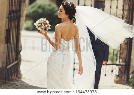 Wind Blows Bride's Veil While She Walks To The Park Gates