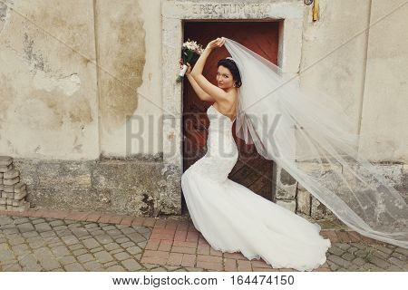 Bride Stands Behind An Old Door While Wind Blows Away Her Veil