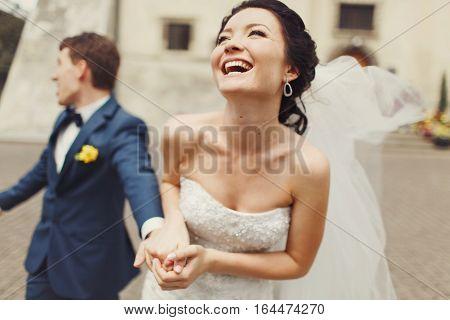Amazing bride laugh sparkling holding groom's hand