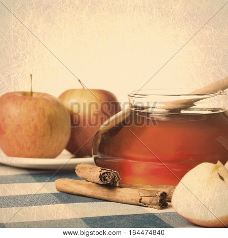 Honey in a jar, cinammon sticks and apples