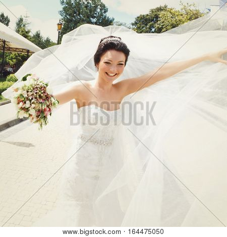 Attractive bride smiles while wind blows her veil