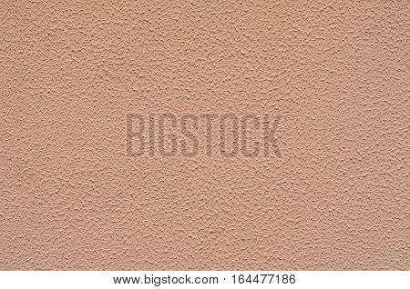 Background of a dark pink stucco coated and painted exterior rough cast of cement and concrete wall texture decorative coating
