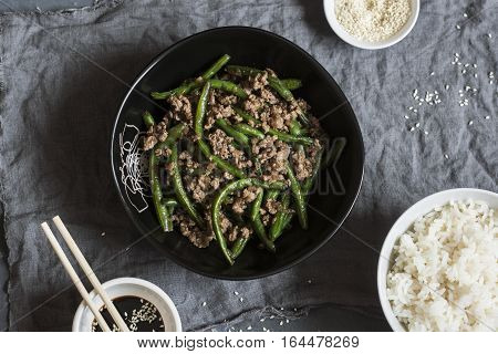 Pork and green beans stir fry and rice on the dark table top view. Flat lay