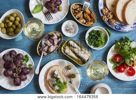 Snacks table - canned sardines mussels octopus grape olives tomato and two glasses white wine on wooden table top view. Flat lay