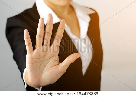 Prohibition symbol. Serious business woman shows stop sign talk to hand gesture on gray blackground.