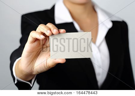 business woman showing a blank empty name card on gray background clipping path