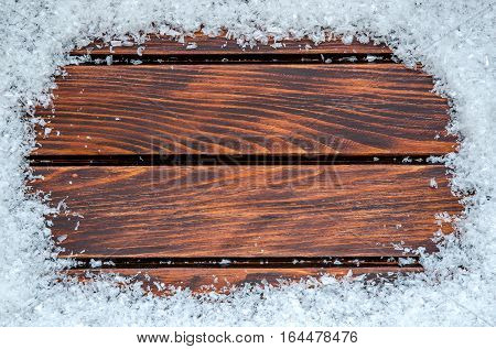 Winter time background. Frame with white snow on a wooden boards.