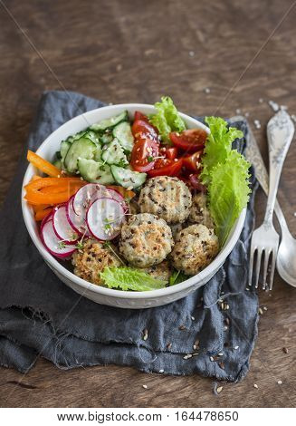 Quinoa meatballs and vegetable salad. Buddha bowl on a wooden table. Healthy diet vegetarian food concept.