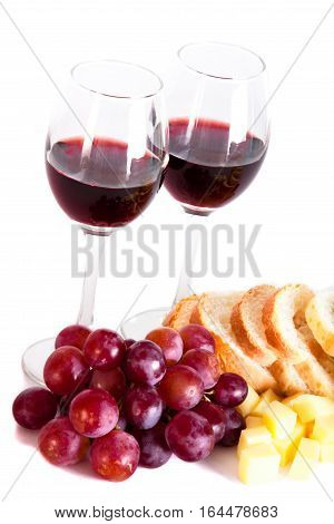 Wine glasses, cheese, grapes and bread isolated