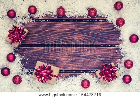 Winter holiday background. Baubles gifts and snow on a wooden boards.
