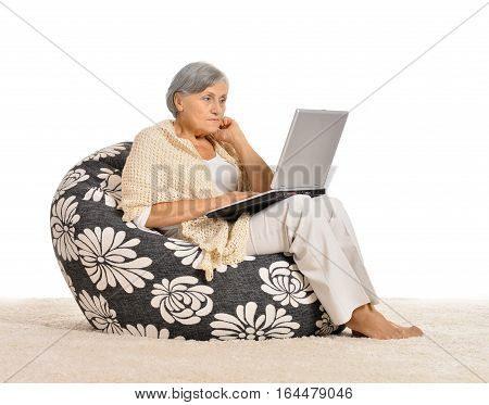 mature woman  using laptop on cozy chair