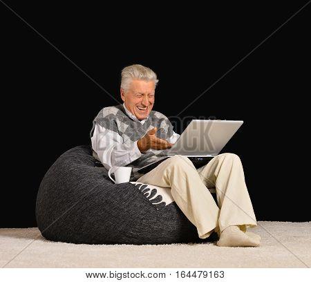 mature man using laptop, ib dark room