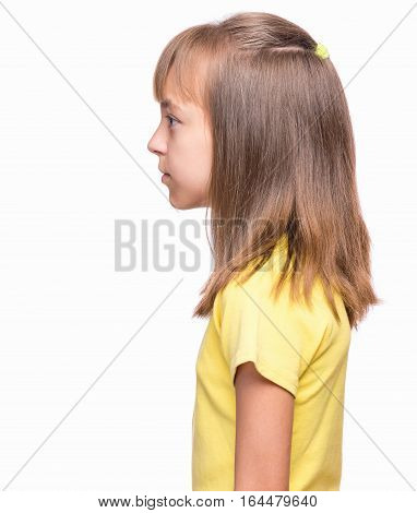 Half-length emotional portrait of caucasian girl wearing yellow t-shirt. Profile of funny cute child, isolated on white background.