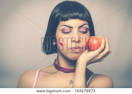 Loving nature. Young woman with apple. Young and beautiful girl with an apple in her hand. Blacks bob hair. On graduated background. Freckles and little heart on the cheek.
