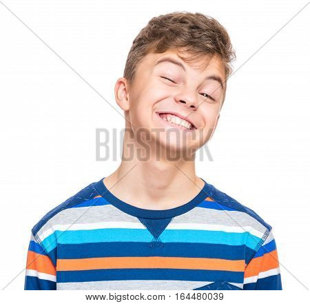 Cute playful teen boy winking at camera - close up emotional portrait. Head shot of handsome young child. Funny cut caucasian teenager, isolated on white background.