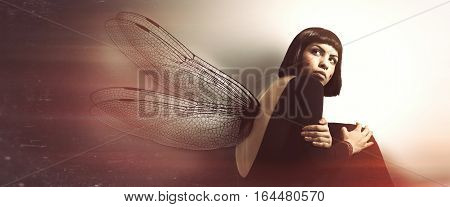 Delicate, feminine fragility. Young woman with wings. Conceptual and artistic image of a young girl with insect wings. Magical atmosphere like in a dream. The young woman is curled up looking behind her. She protects her in a crouching position. Delicacy,