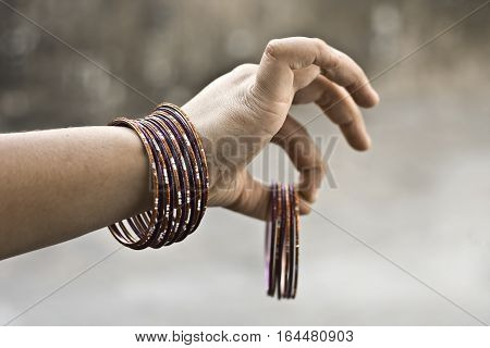 Human hand holding ornaments. viz. Bangles, earrings. etc.