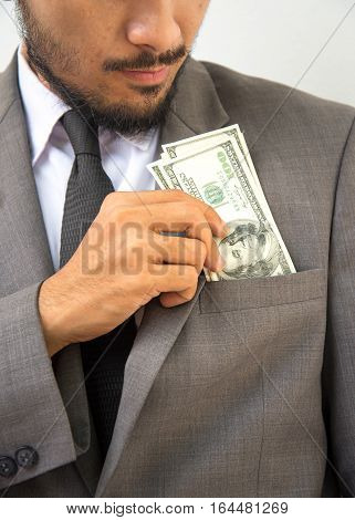 Wealthy handsome. Close-up of young man in putting money in his pocket while standing against grey background