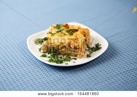 Lasagna with greens on a plate on a blue napkin macaroni with chicken forcemeat