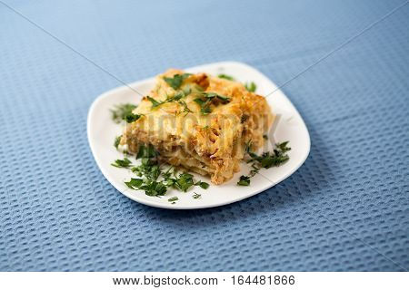 Lasagna With Greens On A Plate On A Blue Napkin, Macaroni With Chicken Forcemeat