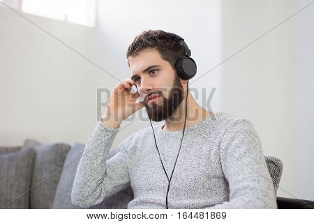 Young man listening relaxation music indoor sitting on sofa