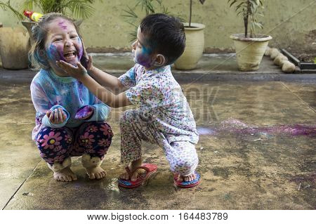 Two Indian kids with their face smeared with colors celebrate Holi, the festival of colors.