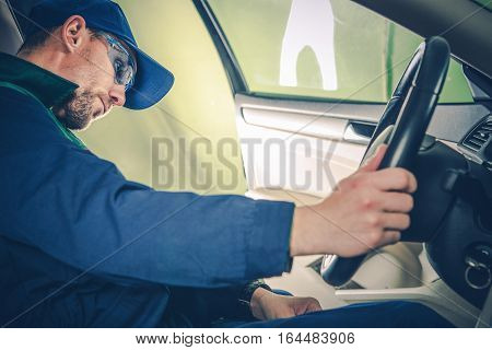 Professional Car Mechanic Examining Electronic Systems of the Car While Seating Inside. Car Maintenance and Inspection.
