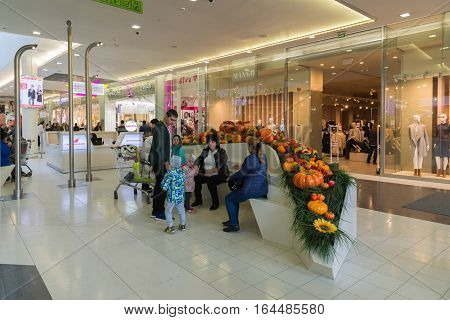 Moscow Russia - October 01.2016. Family resting on a bench decorated with fruits in the shopping and entertainment center Gagarin