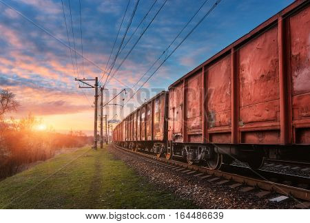 Railway Station With Cargo Wagons And Train At Sunset