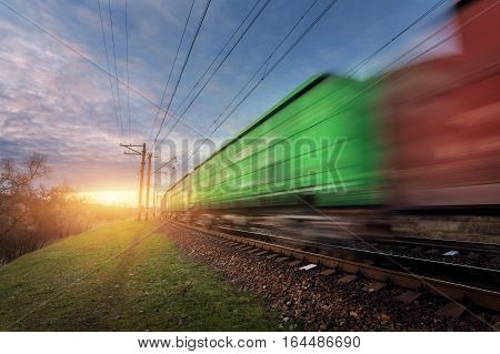 Railway Station With Cargo Wagons In Motion At Sunset