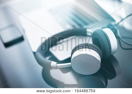 Headphones and the Computer. Online Music Listening Concept Photo with Modern Wireless Headphone and Laptop Computer on Glassy Desk.