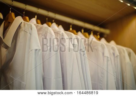 background of row of white shirt hanging in closet