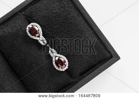 Pair of ruby earrings in black jewel box closeup