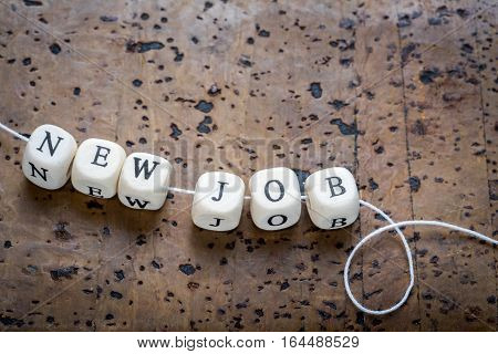 New job text on a wooden cubes strung on a thread on a brown cork background