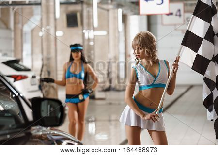 Sexy long haired girls in formula one style tops and mini skirts posing with flags near car at carwash