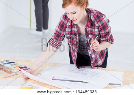 Young and red haired woman designer leaning on desk with interior projects and color picker