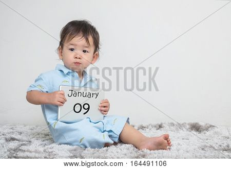 Closeup cute asian kid show calendar on plate in his hand in january 9 word on gray carpet and white cement wall textured background with copy space