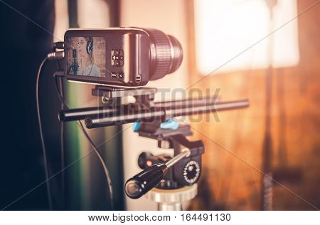 Modern Compact Video Equipment in Action. Small Video Camera on Tripod. Girl Singing to Microphone on the Camera Display.